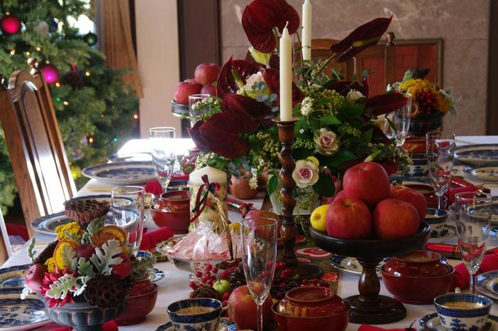 べリック一家が囲むイメージで作られたクリスマスの食卓。漆のお椀があり、画像では見えにくいですが、テーブルセンターには日本の帯が使われています。山盛りのりんごに、温かな家庭の雰囲気が満ちて。