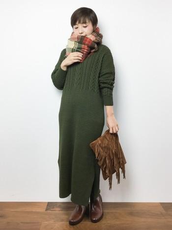 胸元や袖のアラン編みが表情豊かなロングニットワンピース。モスグリーンやフリンジのクラッチバッグがヴィンテージな雰囲気のコーディネートです。