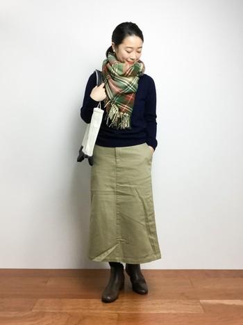シンプルなネイビーのニットにタイトスカートにタータンチェックのマフラーを巻いた優等生スタイル。よ無造作な感じに少し崩してルーズに巻くのがよりおしゃれに見せるコツです。