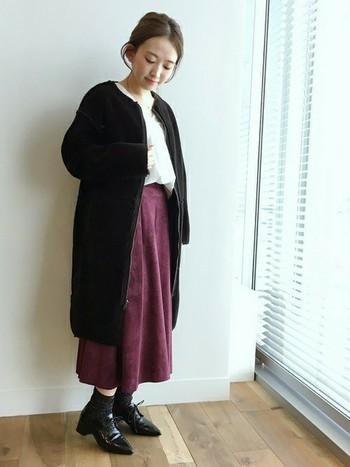 白のトップスに紫のスカートを合わせた甘めのコーデに黒のノーカラーコートを羽織るだけで全体が引き締まって見えます。
