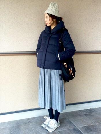 ダウンにプリーツスカートを合わせてカジュアルに。ニット帽は深く被らずに後れ毛を見せたら可愛いですよ。