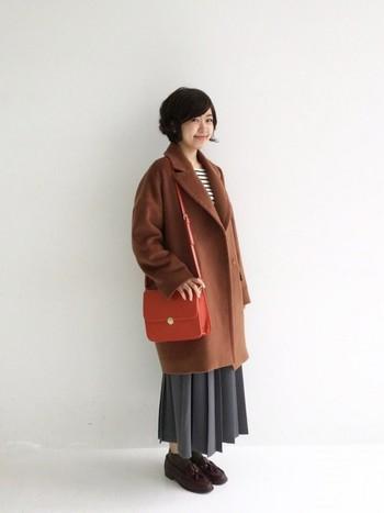 ビッグシルエットコートにプリーツスカートを合わせたクラシカルなコーデ。女性らしいスカートにもビッグシルエットのコートはよく合います。