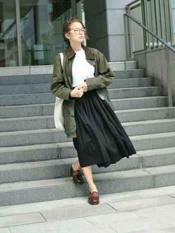 グリーンの大きめ「ビューフォート」に黒のロングスカートと白のトップスを合わせた綺麗めコーデをカジュアルダウン。素足に、襟色と同じブラウン色の靴が大人のヌケ感を演出しています。