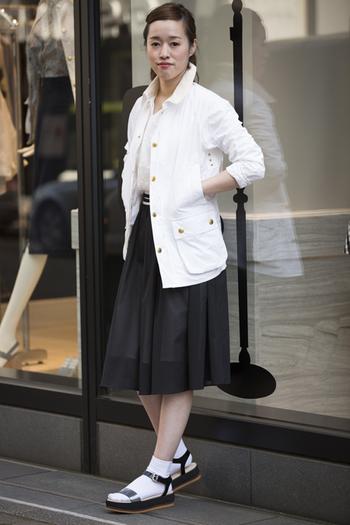 爽やかな白のBarbourジャケットを、白のトップスと黒のスカートでモノトーン調でまとめたスタイル。サンダルとホワイトソックスで、全体が重くなりすぎない印象に。白の明るさが目を惹きます。