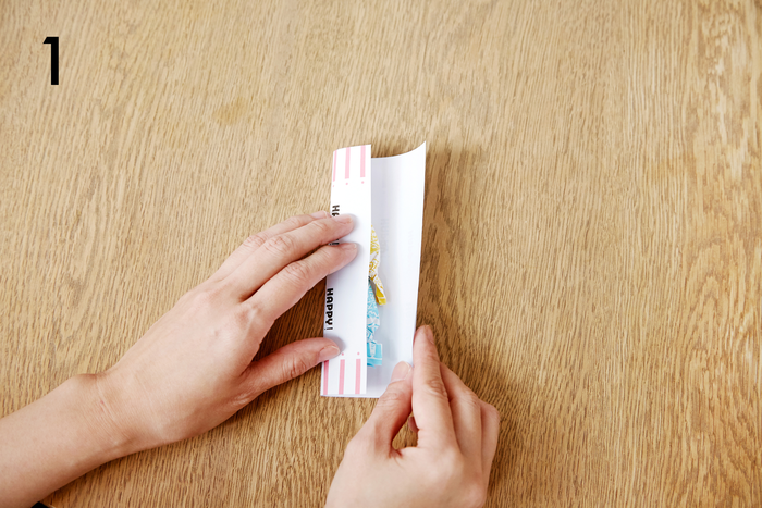 好きなデザインをプリントした普通紙をカットし、中央に包みたいものを置き、両側から包みます ※各デザインは包みたいものの大きさに合わせてレイアウトします。ペーパーの端にアクセントが来るようなデザインが◎!