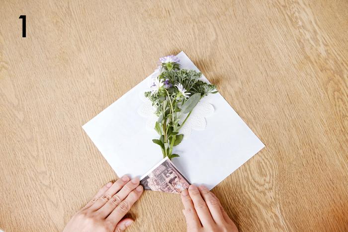 写真を印刷したペーパーを正方形にカットします。 中央にレースペーパーと花を配置し地を内側に折ります