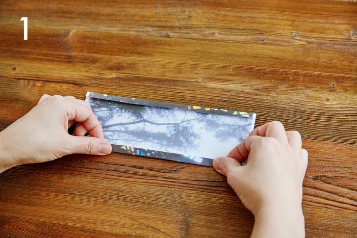 お好みの写真を両面印刷した用紙を横に4分割します。カットした4枚の中から本体部品を1枚選び、天地を1㎝ずつ折って、裏の柄を出します