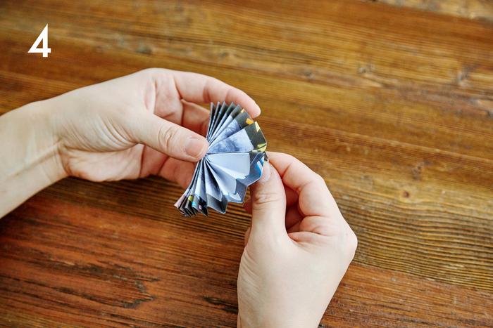 じゃばらに折った3の部品を半分に折り、中央に折り目をつけます。折り目を中心に円になるよう広げて、上下を両面テープで貼り合わせます