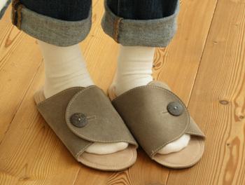 awasefuの人工皮革を使ったスリッパ。ボタンを外すとフラットになりかさ張りません。ふんわりとした質感で足を包みます。洗濯機で丸洗いできるのも魅力。
