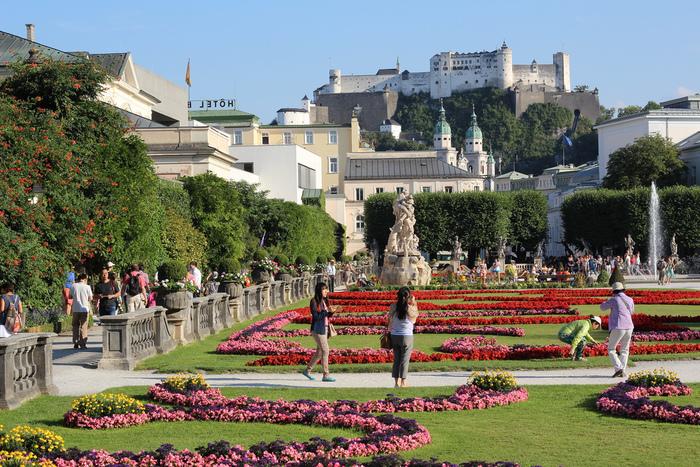 噴水、ギリシア彫刻、色とりどりの花々で装飾された麗しいミラベル宮殿の中庭からは、ホーエンザルツブルク城が見えます。