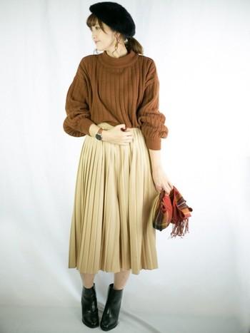 ざっくりニット×今季トレンドのプリーツスカートの大人ガーリーなスタイル。ブラウンカラーのやわらかなコーデに、ブーツとベレー帽のブラックがバランス良く馴染みます。チェックのマフラーがオシャレ度アップのポイント!寒いときはタイツをはいて、色で遊んでみるのもおすすめです。