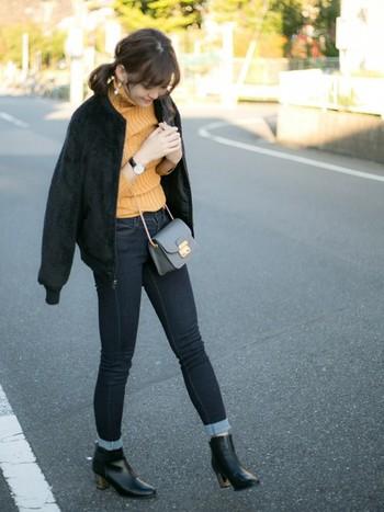 黒ブーツ×デニムでシックにまとめたスタイル。黒を選べば、かっこいい印象になりますね。ロールアップで抜け感プラスも忘れずに♪あたたかみのあるオレンジ色のリブニットに、トレンドのMA-1を羽織った甘辛ミックスコーデに、レディーなポシェットバッグのバランスが◎