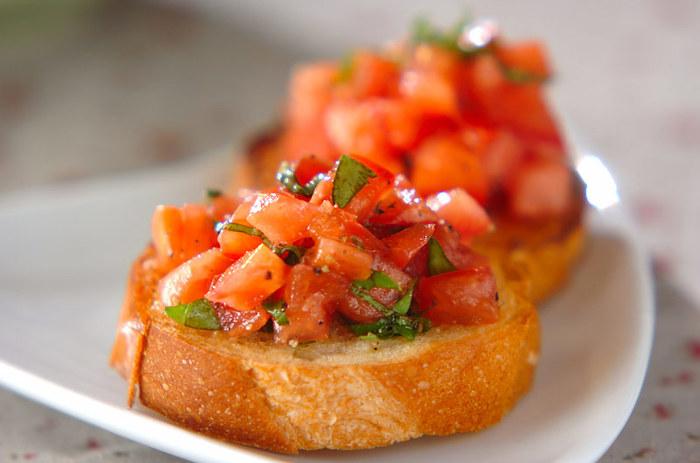 トマトの赤とバジルの緑が食卓を彩る、トマトのブルスケッタです。 バケットのサクサク感がなくなってしまうのでトマトは食べる直前にバケットにのせること、トマトの水気はしっかりと切っておくことがポイントです。
