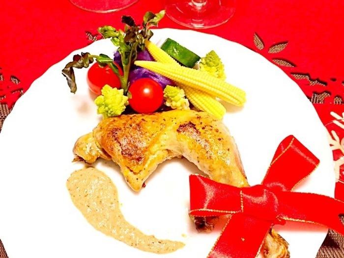 赤いリボンをあしらってクリスマス感をアップ♡フライパンでできちゃう簡単ローストチキン。チキンは焼いてから蒸すので外はパリっと、中はふんわり仕上がります。