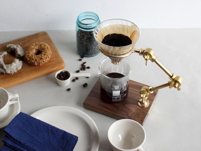 """まるで実験道具のような佇まいのドリッパースタンドは、コロラド州フォートコリンズのTHE COFFEE REGISTRY(コーヒーレジストリー)によるもの。アームの高さや角度を調節すれば、背の高いサーバーから一人用の小さなカップまで、さまざまなアイテムと合わせることが可能です。組み立て式のアームや、真鍮とウォルナットの重厚感ある風合いが""""本物""""を感じさせ、きっと男心をくすぐるはず。  こちらはアームに節のある「Curator pour over stand」です。"""