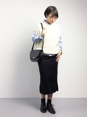 爽やかなブルーのオックスフォードシャツには白ニットを重ねてレイヤードスタイルに。ブラックのタイトスカートを合わせたオフィスカジュアル風な着こなしが素敵。