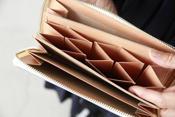 レザーの持ち手が付き、開閉もスムーズ。カード類は縦向きに入れる珍しいデザインですが、これがとても取り出しやすく、一目でどのカードか分かるので便利です。外側・内側の配色のコントラストも効いていますね。 機能性とデザインを両立した財布を自分のために…。あなたは何色を選びますか。