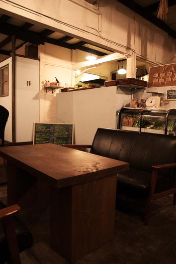 白い壁とブラウンの床、そして木のテーブルのある、飾りすぎないおしゃれな空間です。壁や天井には草花が飾られており、オーガニックレストランの雰囲気を高めています。