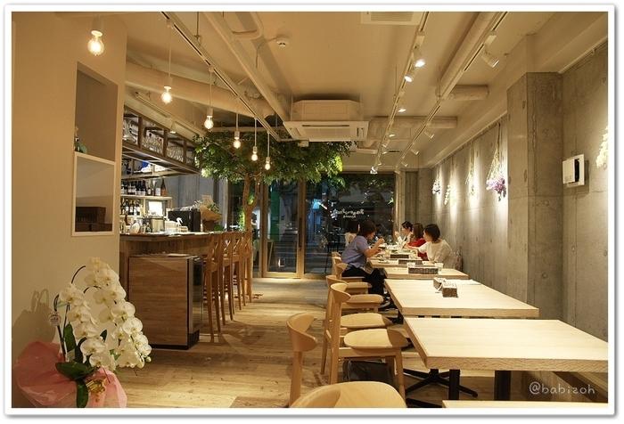 店内の雰囲気はナチュラルで、カウンター横の木がアクセントになっています。椅子やテーブルが明るい木でできているのでコンクリートの壁も冷たい印象にならず、とても落ち着いた空間です。