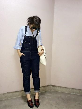 爽やかなブルーのオックスフォードシャツとデニムのオールインワンを合わせて。足元はポインテッドローファーで大人っぽくまとめて。