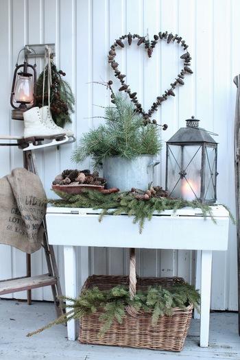 ハート型のワイヤーに木の実をアレンジしたリース。ランタンやスケート靴など冬小物を上手く組み合わせています。