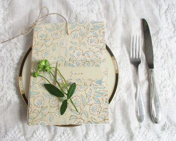 席次表やメニュー表にぴったりな、ブロックプリントで丁寧に仕上げたシルキーペーパーのカバー。淡い色合いの花柄が優しく上品です。麻ひもや手漉き紙がセットされてナチュラルな雰囲気もプラスされます。