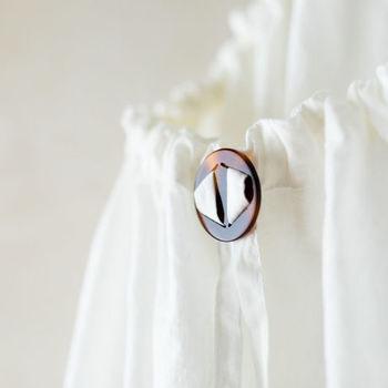 襟ぐりの大きさが調節できる首元のパーツは、メガネに使われる自然素材を加工したオリジナルのものが使われています。まるでブローチのような、とっても素敵なワンポイントとなっています。