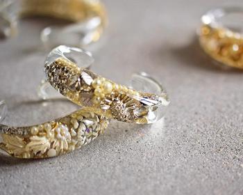 海外のアンティークパーツをアクリル樹脂に閉じ込めた、存在感抜群の「RUKA(ルカ)」のブレスレット。  まるで氷の中に宝石やお花が透けて見えているかのよう。ハンドメイドで丁寧に作られた、デザイナーのこだわりが詰まった作品。この、ゴールド×ホワイトとシルバー×ホワイトの色合いは、セレクトショップ「aranciato」の別注品です。