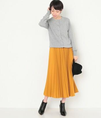 グレーのカーディガンは、綺麗なイエローのスカートとも相性が良いですね。シンプルな丸首カーディガンは定番アイテムとして役立つので、一枚持っておくのがおすすめです。