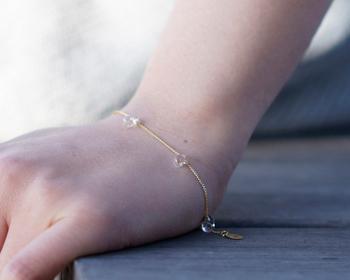 水滴をモチーフにした、「HARIOランプワークファクトリー」の「Water Drops(ウォータードロップス)」シリーズのブレスレット。  ピュアなガラスの粒が所々に散りばめれらた華奢なデザイン。繊細な肌なじみのいいゴールドチェーンは、輪の状態のままで腕に通すことができるので、忙しい朝にもうれしいですね。