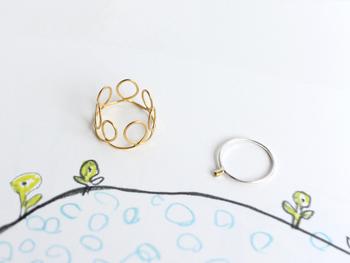 「yo-mi-mi(ヨミミ)」のモリタエミさんが作るリングはどれも可愛らしさとぬくもりに溢れています。  写真左のくるくるリングはラフな曲線が優しく女性らしい印象。写真右のぽっちリングは、主張しないさり気なさの中にもゴールドの凛とした輝きが感じられます。