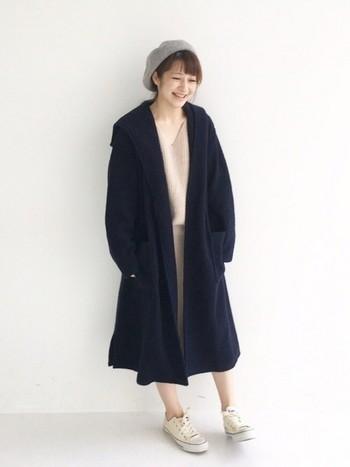 セットアップ風のワンピースとベレー帽、スニーカーを淡いトーンで揃え、ネイビーのコートを軽やかに見せています。