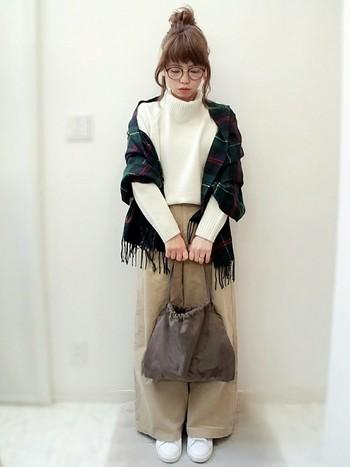 白ニットにベージュ系のパンツと巾着バッグを合わせたコーディネートは、女性らしい柔らかさがありますね。