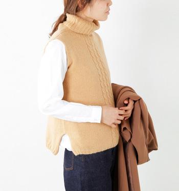 ソフトに編まれたリブ編みは、首周りをふんわりと包み込み、フロントのケーブル編みとともに、やさしい表情を添えてくれます。さらに、ゆるやかに広がるAラインシルエットで程よい女性らしさを演出。シャツやデニムと合わせても、きれいめな大人カジュアルにきまります。