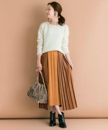 切り替えが入った個性的なデザインのプリーツスカートを合わせています。真っ白なモヘアセーターとのバランスもよく、どちらのアイテムも各々の個性が引き出されています。