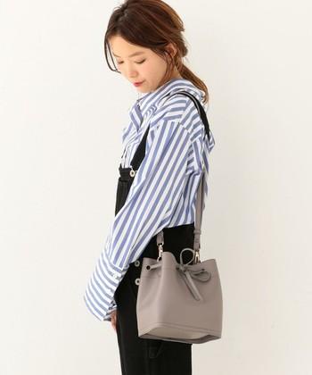 ブルーのストライプシャツがマニッシュな印象のコーデにはミディアムグレーのバッグで華やかさをプラス。