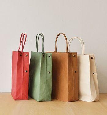 紙製ショッピングバッグのカタチと表面の質感を模した革製トートバッグ。革の裏側に紙の芯を貼り、紙のような質感を出したユニークなトートです。使い始めはクシュッとした「紙」のような質感を、そして使い込むほどに「革」ならではのソフトな質感を楽しむことができます。