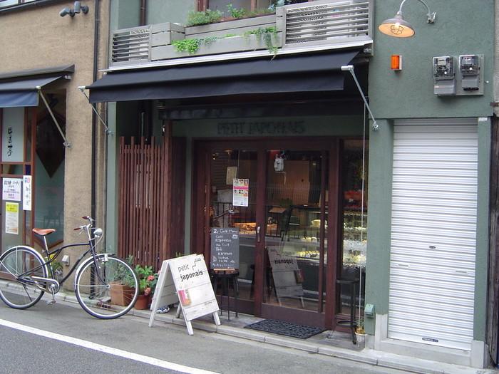 京都のオフィス街、四条烏丸を少し入った所に店舗を構えるプチジャポネ。タルト系を中心としたフランス菓子、焼菓子の小さなお店。2階のカフェでは、ケーキとお茶を頂く事が出来ます。白い木の看板が目印です!