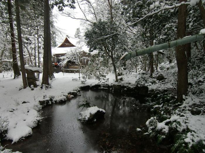 """【画像は雪に覆われた「有清園」。奥の建物が「極楽往生院」。手前の水は""""福寿延命の水""""として知られる「金色水」。】"""