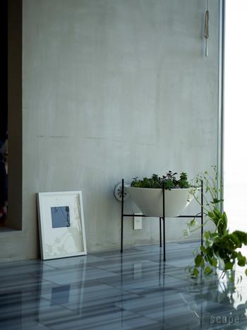 無機質なコンクリートの壁にポスターをさりげなく立てかけると、存在感のある空間が出来上がります。床に映りこんだポスターが素敵ですね。