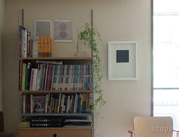 シンプルな白い額がお部屋をぱっと明るく見せてくれます。本棚と壁の縦のラインに連続性があり、美的感覚に訴えかけます。