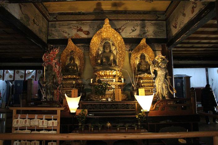 【本堂に安置されている来迎院の本尊、薬師(中央)・釈迦(右)・阿弥陀(左)の三如来坐像。二体の脇侍は、不動明王(左)と毘沙門天(右)。】