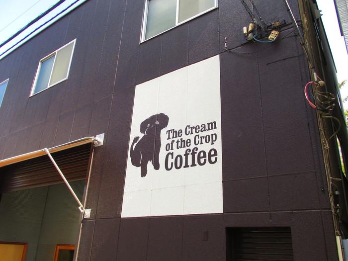 かわいい犬のロゴが目印。まるで倉庫のような外観の、知る人ぞ知るコーヒー専門店「The Cream of the Crop Coffee(ザクリームオブザクロップコーヒー)」。天井の高い店内は、本格派の大きな焙煎機やコーヒー豆がずらり。この珍しい焙煎機を見に来る人もいるという、コーヒー好きが集うお店です。