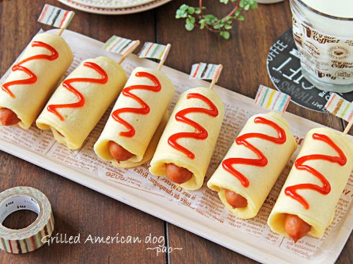 ホットケーキミックスとお豆腐を使って揚げずに作るアメリカンドッグ。ウインナーに爪楊枝を刺したり、皮をくるくる巻いたり楽しく作れそうですね♪