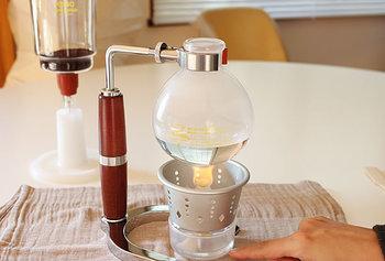 ② ランプに火を付けます。  フラスコのお湯がロートに全て上がったら、竹べらでコーヒーの粉とお湯を馴染ませるように、優しく混ぜます。