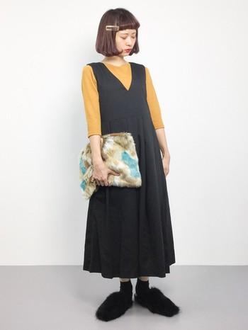 からし色のトップスと、ジャンパースカートを合わせた大人可愛いスタイル。