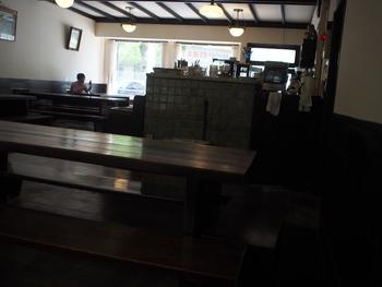 重厚な木製テーブルは人間国宝の黒田辰秋作。壁にかかる絵画や薄暗い店の奥に見える中庭など、すべてが趣深い空間。 タイムスリップしたようなノスタルジックな感覚を覚えます。