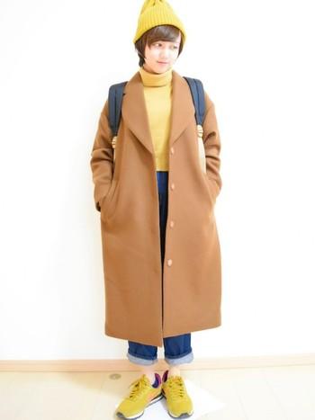ブラウンのコートにからし色のニット帽とセーターとスニーカー。色を合わせてまとまりのあるコーデに仕上げています。