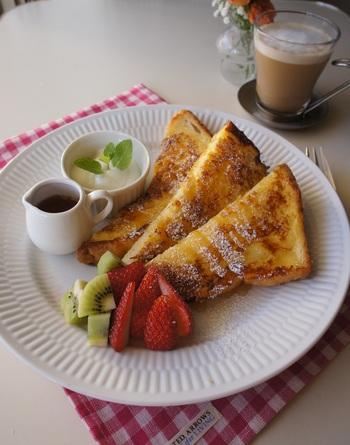 フレンチトーストにフルーツを添えて。かたくなってしまった食パンも有効活用できて◎。メープルシロップをたっぷりかけて召し上がれ。