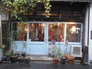たくさんの植物に囲まれたきれいなブルーの引き戸が目を惹く、レトロな外観。おばあちゃんの家を訪ねるかのような雰囲気。昭和4年に出来た長屋を改築して作られた、喫茶・書店・ギャラリーを兼ねたお店です。